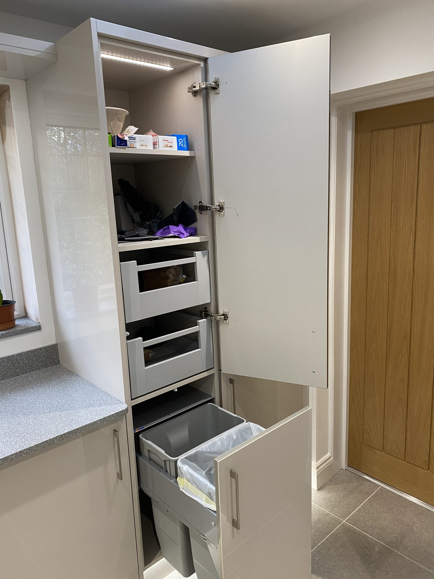 Pull out bin set in tall larder with internal drawers