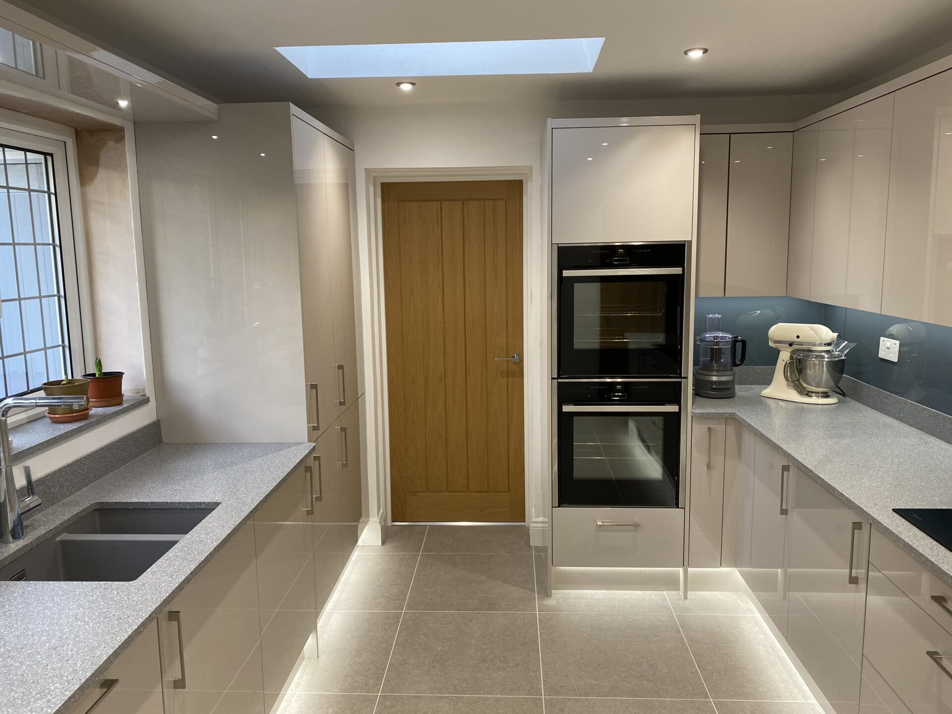 Ultra gloss cashmere kitchen with Handle less wall cabinets and solid acrylic wortops fitted in Wellington Telford